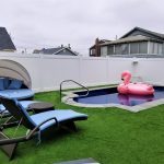 In-ground pool surrounded by turf grass, large pink flamingo float in pool, and white vinyl privacy fence around