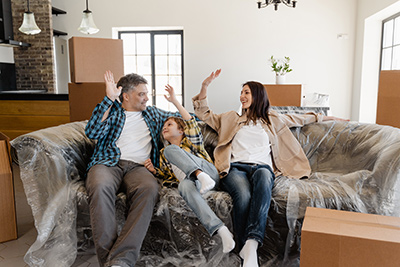 Lavallette real estate makes families happy like this trio high fiving on a couch surrounded by moving boxes