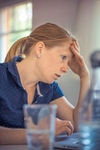 Ortley Beach real estate home buyer looking stressed while using laptop