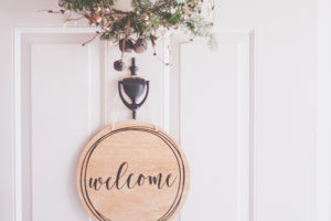 """Seaside Park rental white door with bottom of winter wreath showing and wooden circular tag hanging with word """"welcome"""" written on it"""