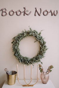 Ortely Beach real estate image of evergreen wreath on wall behind table with gold chapagne bucket, 4-candle holder, and pink vase.